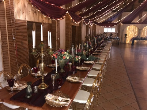 Wedding reception hall decorated in rose gold and naked teak tables
